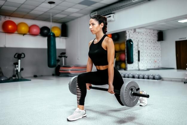 バーベルで突進運動をしている魅力的な女性