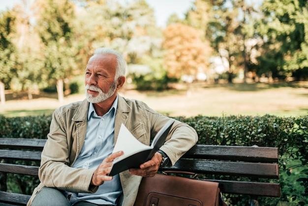 屋外の本を読んでハンサムな中年の男性。