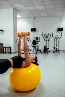 若い女性がジムで重みを保持しているピラティスボールを行使します。