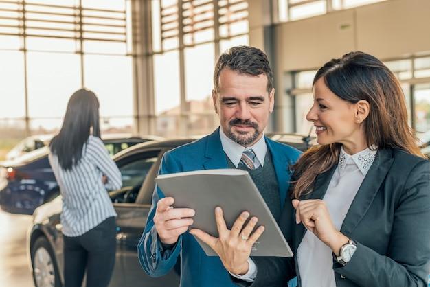 車のディーラーが顧客に車のファイルを表示します。