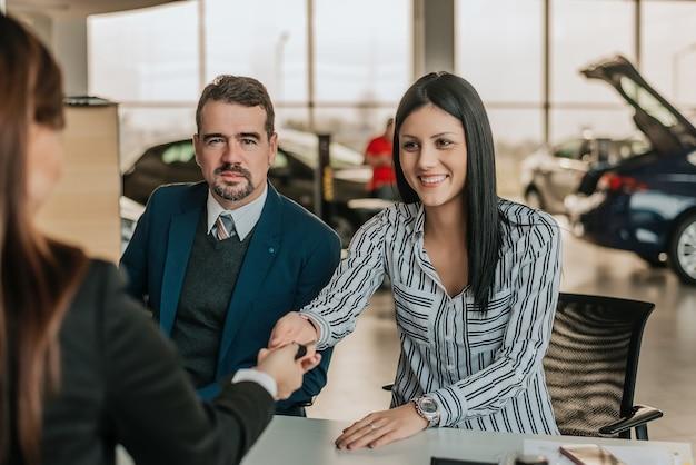 Красивая женщина клиента рукопожатие с продавщицей.