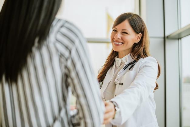 Женский доктор говорить и трогательно пациентка для поощрения.