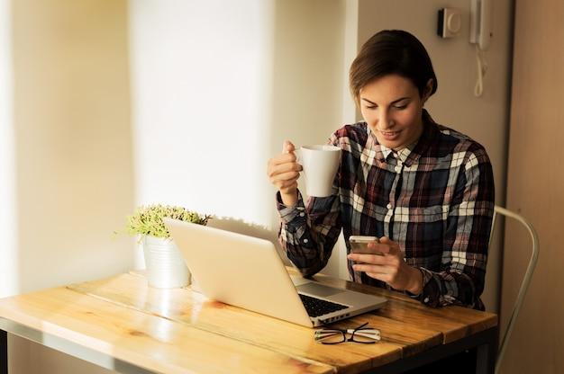 Снятый милой молодой женщины обмениваясь сообщениями от домашнего офиса пока имеющ чашку кофе