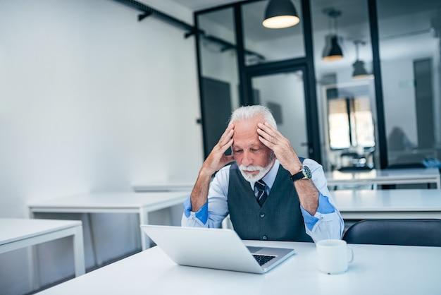 ノートパソコンを見ながら頭を抱えて心配しているシニアビジネス男。