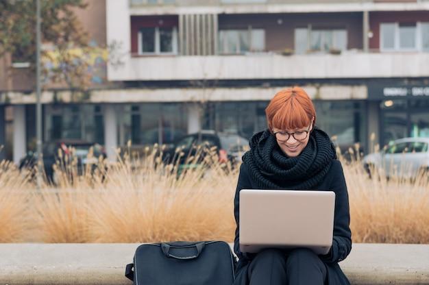 外のコンピューターで働くビジネス女性