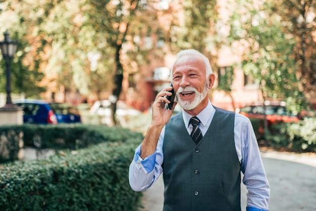 街でスマートフォンで話している年上のビジネスマンの笑みを浮かべてください。
