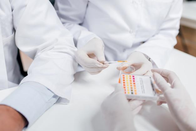 実験室でストリップを用いて試料採取する。