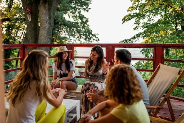 Друзья веселятся на деревянном балконе в лесу.