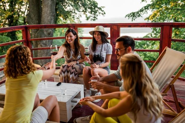 友達が屋外で乾杯します。木製テラスに座っています。