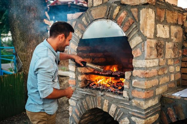 夏のお楽しみ。若い男がレンガのバーベキューで肉を料理します。