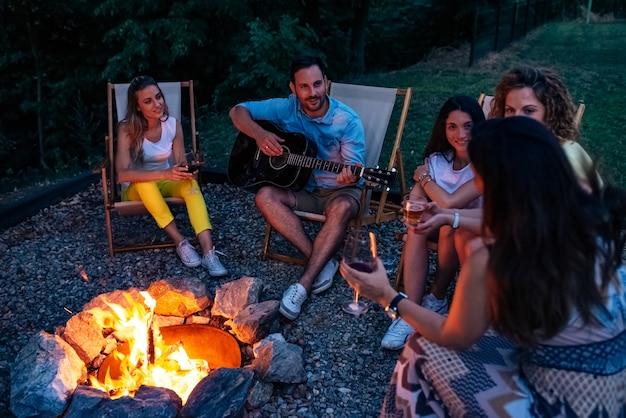 キャンプファイヤーの周りに楽しい時間を過ごしている友人のグループ。