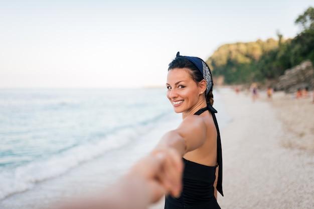 フォローしてください。男の手を握って幸せな若い女。カップルはビーチの上を歩きます。
