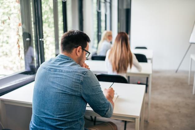 大学生が試験に参加します。背面図