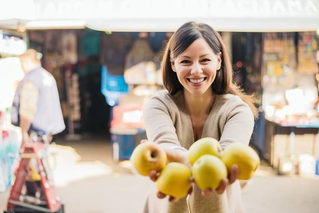 Клиент женщины держа яблока на зеленом рынке.