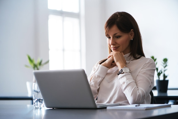 オフィスのラップトップで働く若い笑顔の女性。