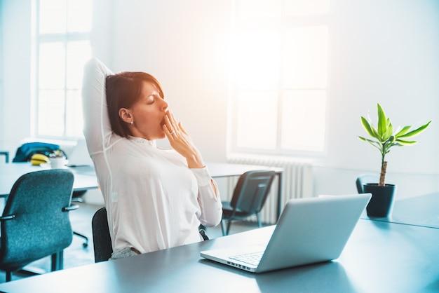 あくび、オフィスの机で働く疲れて眠そうな女性。