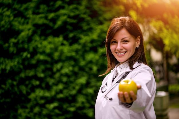 Женский доктор предлагая яблоко