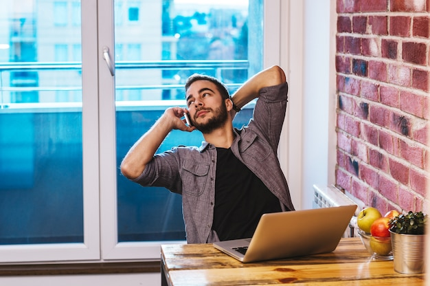 Портрет улыбающегося человека, выступая на мобильном телефоне, сидел на столе.