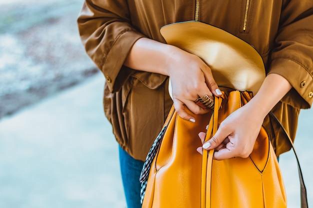 Элегантный наряд. закройте стильный оранжевый рюкзак в руке женщины.