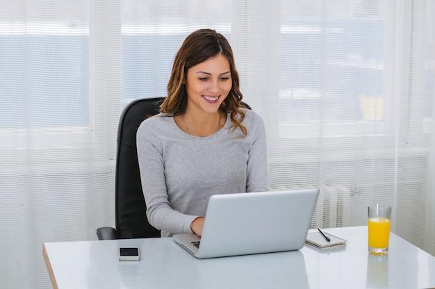 Красивая молодая женщина фрилансер, используя портативный компьютер