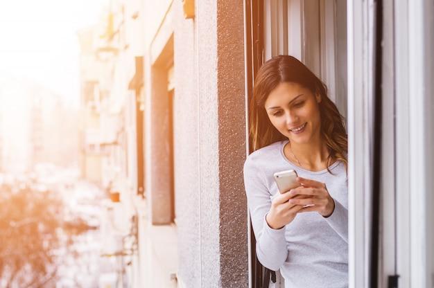 Молодая коммерсантка используя мобильный телефон пока смотрящ окно.