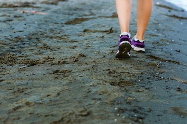 女性の足のクローズアップ、ビーチを走る女性。