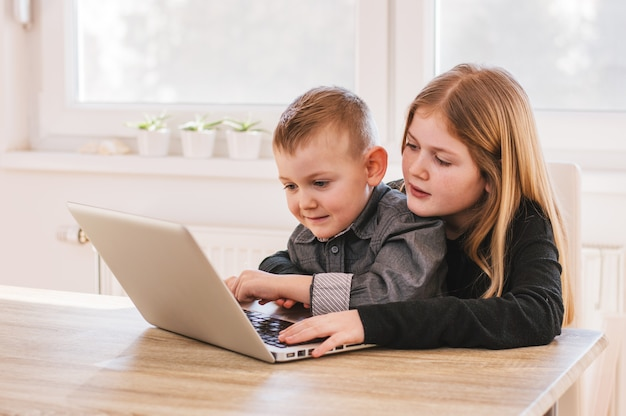 兄と妹が自宅のコンピューターでゲームをプレイ
