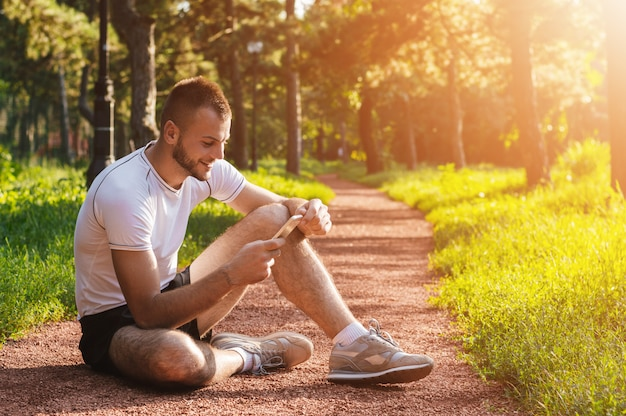アスリートやスポーツのトレーナーが公園で彼の携帯電話をチェック