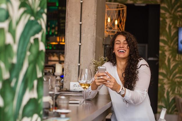 Девушка с красивой улыбкой читает смешное сообщение на своем смартфоне в кафе