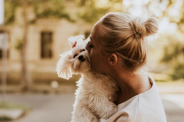 Портрет молодой женщины, держащей и целующей мальтийскую собаку