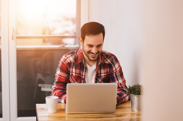 成功した起業家は彼がホームオフィスで働いている間彼のラップトップコンピューターで情報をチェックするので満足に微笑んでいます。レンズフレア