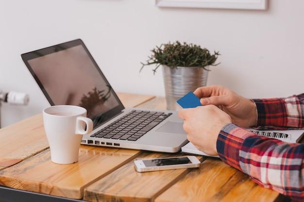 Мужские руки, держа кредитную карту и покупки в интернете