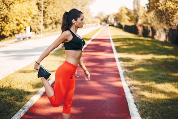 女性ランナーの音楽を聴くとジョギングをする前にウォームアップ。