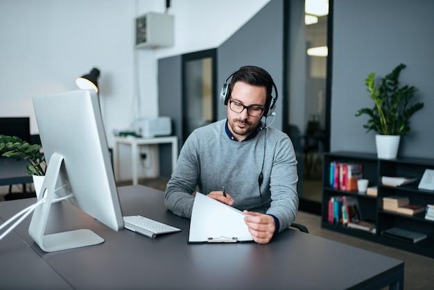 クライアントに話している間彼のファイルを見て若いカスタマーサポートオペレーター。
