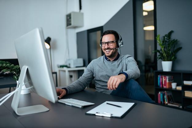 ヘッドセットを介してオンラインで話しているハンサムなカジュアルなビジネスマン。