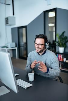 近代的なオフィスにビデオ通話を持つカジュアルなビジネスマン。