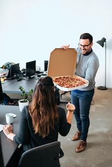 職場で昼休みを過ごしている空腹の同僚。ピザを食べます。