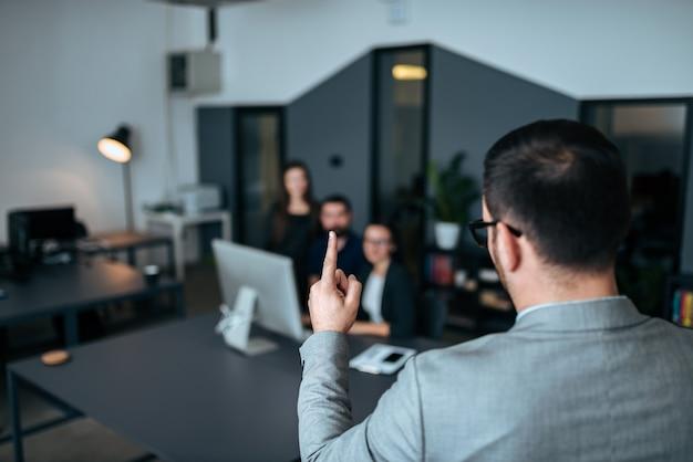 ビジネス会議で同僚に話しているビジネスマンの背面図。
