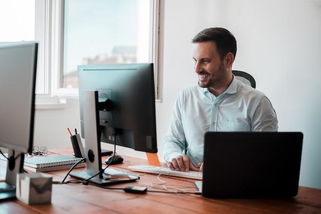 コワーキングオフィスで働くハンサムな男の笑みを浮かべてください。コンピューターの前に座っています。