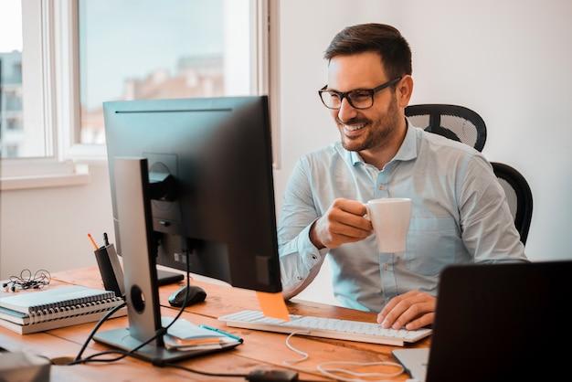 ハンサムな男のホームオフィスでコンピューターのモニターを見ながらコーヒーを飲みます。