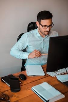 В поисках вдохновения. заботливый молодой человек записывая идеи пока сидящ на столе офиса.