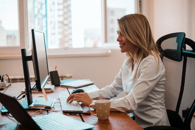 Взгляд со стороны молодой женщины работая на дому-офисе.