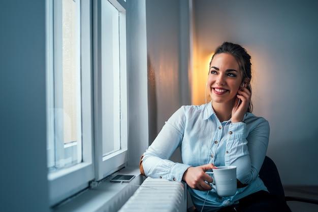 女性は窓の近くでリラックス、音楽を聴きます。