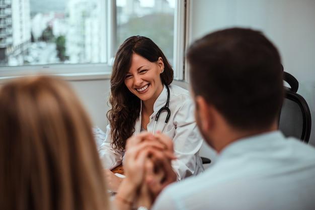 若いカップルと相談若い医者を笑顔します。