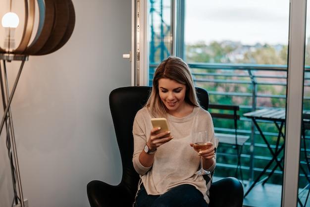 自宅で座っていると彼女の携帯電話を使用して笑顔の金髪女性の肖像画。