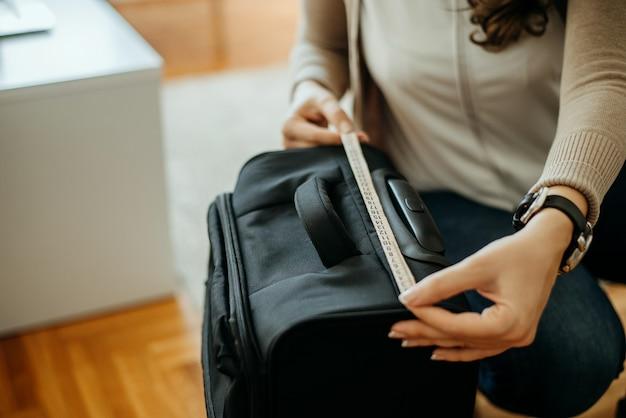 Женщина измерения размера багажа.