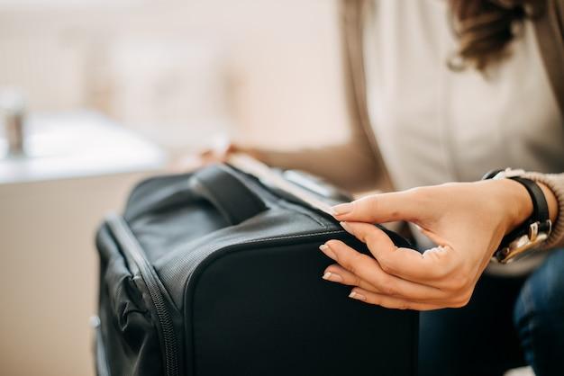 Крупный план женщины используя измеряя ленту для того чтобы измерить багаж кабины.