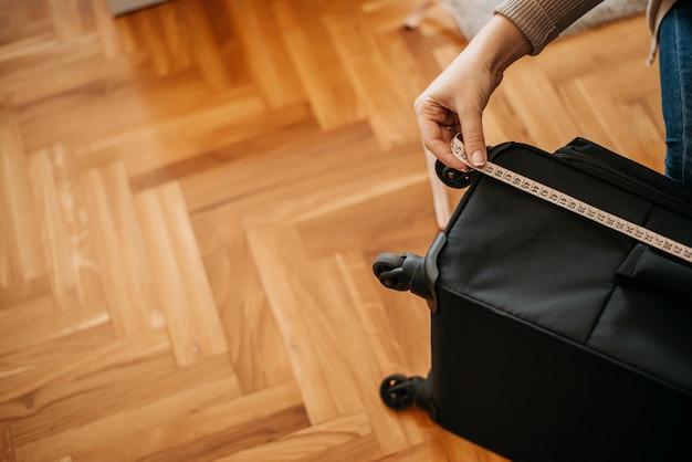 Крупным планом женщина измерения багажа.