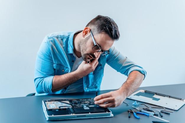 ラップトップコンピューターを修復しながら携帯電話で話しているハンサムなコンピューターエンジニア。