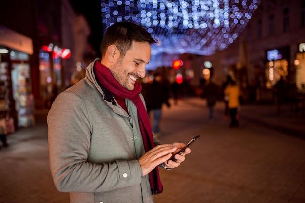 クリスマスの装飾が付いている通りに携帯電話を持つ若い男の笑みを浮かべてください。